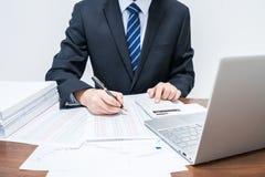 Uomini d'affari che utilizzano il calcolatore che fa la contabilità fotografia stock