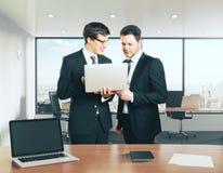 Uomini d'affari con il computer portatile che discutono qualcosa nell'ufficio Fotografia Stock Libera da Diritti