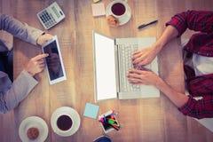 Uomini d'affari creativi che lavorano agli apparecchi elettronici Immagini Stock