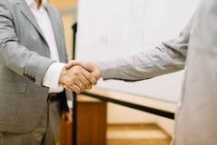 Uomini d'affari del primo piano che stringono le mani su un fondo vago Concetto di accordo Fotografia Stock Libera da Diritti