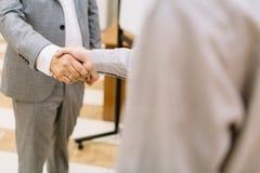 Uomini d'affari del primo piano che stringono le mani su un fondo vago Concetto di accordo Immagini Stock