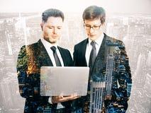 Uomini d'affari facendo uso del computer portatile immagini stock libere da diritti