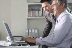 Uomini d'affari facendo uso del computer portatile allo scrittorio Fotografie Stock