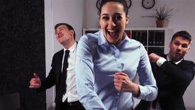 Uomini d'affari felici pazzi e dancing della donna di affari nell'ufficio archivi video