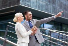 Uomini d'affari sorridenti con il pc della compressa all'aperto Fotografia Stock Libera da Diritti