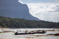 Uomini dei pescatori che spingono una barca di legno nel fiume Canaima, Venezue Fotografia Stock