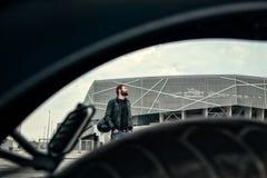 Uomini del motociclista con una barba che sta sulla via Immagini Stock