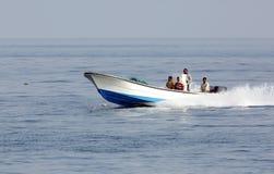 Uomini del pescatore di primo mattino che si muovono nel mare sul motoscafo Fotografie Stock