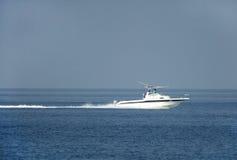 Uomini del pescatore di primo mattino che si muovono nel mare sul motoscafo Fotografia Stock