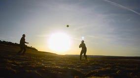 Uomini di addestramento nella pallavolo sulla spiaggia al sole, beach volley sulla sabbia sulla sera della molla stock footage