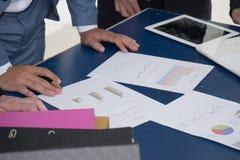 Uomini di affari che esaminano rapporto in carta sulla tavola per discutere abou immagine stock