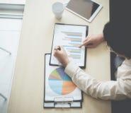 Uomini di affari che si incontrano ed inclusi un grafico nel business plan fotografia stock