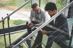 Uomini di affari che si siedono sulle scale Gente di affari che ha conve Fotografia Stock