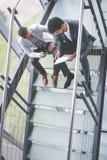Uomini di affari che si siedono sulle scale Gente di affari che ha conve Immagine Stock Libera da Diritti