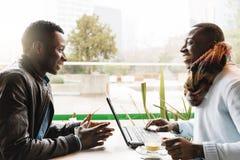 Uomini di affari che utilizzano cellulare e computer portatile nella caffetteria Immagine Stock