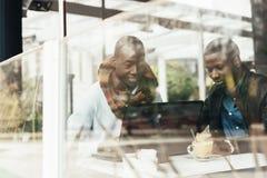 Uomini di affari che utilizzano cellulare e computer portatile nella caffetteria Fotografie Stock Libere da Diritti