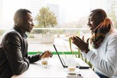 Uomini di affari che utilizzano cellulare e computer portatile nella caffetteria Fotografia Stock