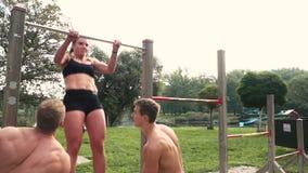 Uomini e donna che fanno i vari esercizi di peso corporeo alla barra orizzontale archivi video