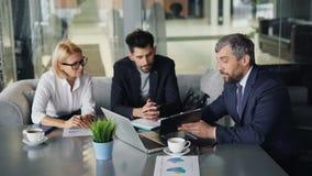 Uomini e donna delle persone di affari che parlano in caffè che esamina le carte e computer portatile video d archivio