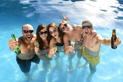 Uomini e donne attraenti felici in bikini che ha bagno alla birra bevente della piscina della località di soggiorno dell'hotel Fotografia Stock