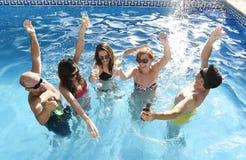 Uomini e donne attraenti felici in bikini che ha bagno alla birra bevente della piscina della località di soggiorno dell'hotel Immagini Stock