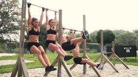 Uomini e donne che fanno i vari esercizi di peso corporeo alla barra orizzontale video d archivio
