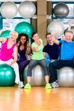 Uomini e donne che si siedono sulle palle di forma fisica in palestra fotografia stock