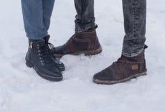 Uomini e le scarpe delle donne su fondo di pietra snowal Frammento di una parete da una pietra scheggiata immagini stock