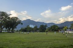 Uomini e ragazzi in vestiti variopinti che giocano a calcio sull'erba verde contro un fondo degli alberi e fotografia stock