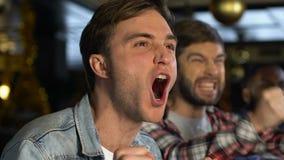 Uomini emozionali in pub felice circa il gioco di conquista favorito del gruppo di sport, supporto stock footage