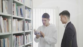Uomini felici dell'università che ridono e che abbracciano quando uno di loro ha trovato il libro stock footage