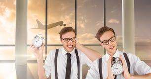 Uomini gemellati dei pantaloni a vita bassa che tengono gli orologi in aeroporto fotografia stock
