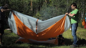 2 uomini hanno impilato la tenda arancio Giorno soleggiato di estate nella foresta archivi video