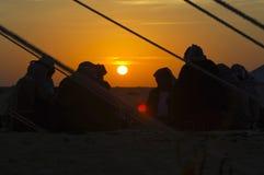 Uomini intorno ad un posto del fuoco nel deserto ad alba Fotografie Stock Libere da Diritti