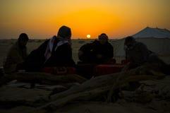 Uomini intorno ad un posto del fuoco nel deserto ad alba Immagini Stock Libere da Diritti