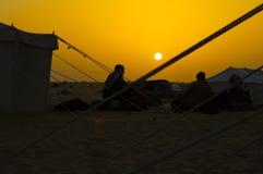 Uomini intorno ad un posto del fuoco nel deserto ad alba Immagine Stock Libera da Diritti