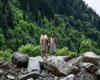 Uomini locali che stanno sulla roccia con la foresta del pino fotografia stock