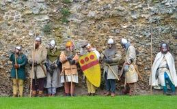 Uomini medievali alle armi contro la vecchia parete Fotografia Stock Libera da Diritti