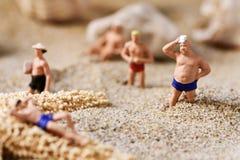 Uomini miniatura in costume da bagno sulla spiaggia Immagine Stock Libera da Diritti