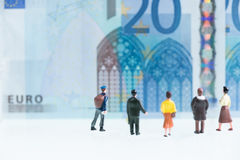 Uomini miniatura e donne che esaminano precedenti di 20 gli euro banconote Fotografie Stock Libere da Diritti