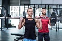 Uomini muscolari che sollevano un bilanciere Immagini Stock Libere da Diritti