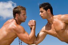 Uomini muscolosi sotto il cielo blu Fotografia Stock Libera da Diritti