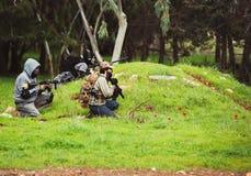 Uomini nei militari con l'arma Immagine Stock