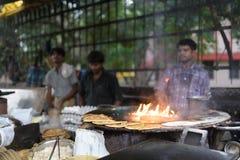 Uomini non identificati che cucinano pane piano indiano nel mercato Fotografia Stock