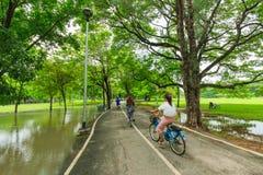 Uomini non identificati e donne che ciclano e che camminano nel parco del parco o del treno di Vachirabenjatus a Bangkok Tailandi fotografia stock