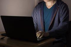 Uomini o maschio che lavorano o che giocano il computer portatile del computer portatile al buio Immagini Stock