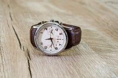 Uomini, orologi con la cinghia marrone su fondo di legno fotografia stock