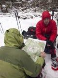 Uomini in racchette da neve che guardano mappa nella foresta di inverno Fotografie Stock