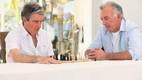 Uomini senior degli amici che giocano scacchi stock footage