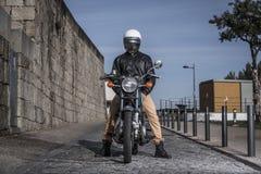 Uomini sul suo motociclo con il casco immagini stock